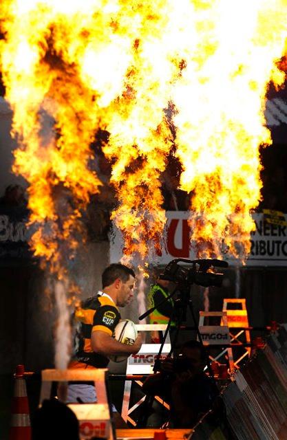 A Taranaki player seen through the TAG Oil stadium flares.